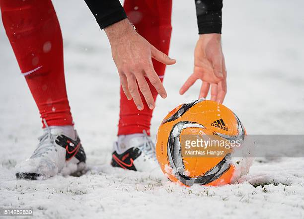 A players picks the snowy ball during the Second Bundesliga match between SC Freiburg and RB Leipzig at SchwarzwaldStadion on March 7 2016 in...