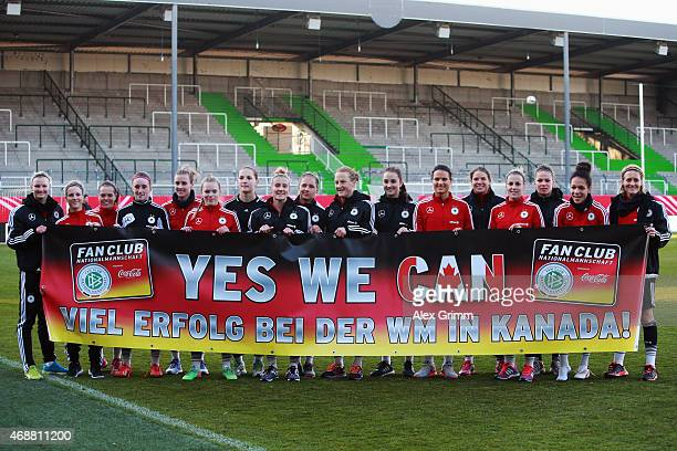 Players pose with a banner after a Germany training session ahead of their friendly match against Brazil at Sportpark Ronhof on April 7 2015 in...