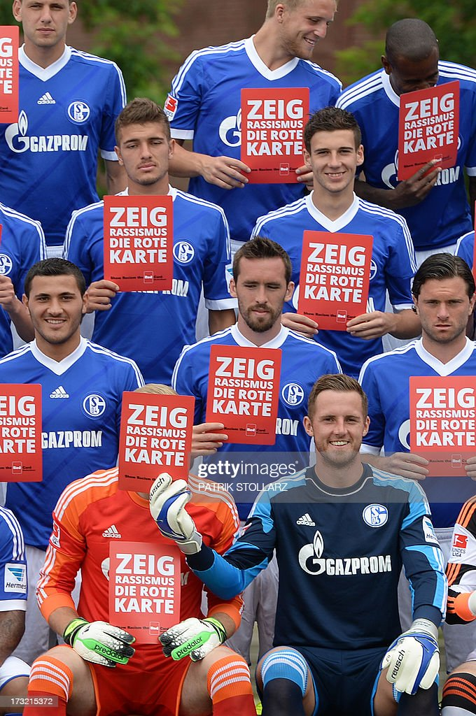 Players pose with red cards against rassicm during a team photo call of German first division Bundesliga football club Schalke 04, on July 10, 2013 at the grounds of the former coal mine 'Consolidation' in Gelsenkirchen, western Germany.