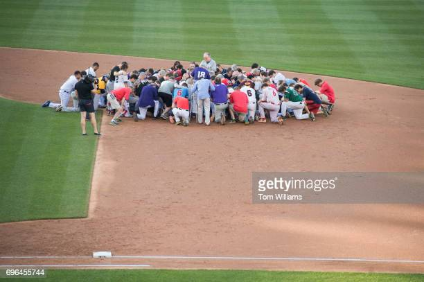 Players pray for the victims of the shooting at the Republican baseball practice before the 56th Congressional Baseball Game at Nationals Park on...