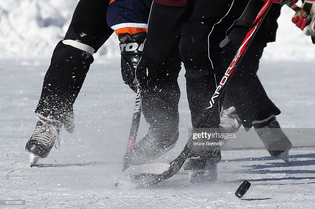 Players pursue the puck in the 2013 USA Hockey Pond Hockey National Championships on February 8, 2013 in Eagle River, Wisconsin. The three-day tournament features 2,400 participants from 30 states playing a round robin tournament on 28 rinks laid out on Dollar Lake.