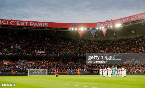 TOPSHOT Players referees and supporters observe a minute silence in tribute to the victims of Barcelona's attacks prior to the French L1 football...