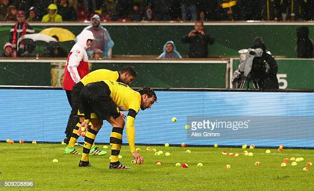 Players remove tennis balls thrown by Dortmund fans from the pitch during the DFB Cup Quarter Final match between VfB Stuttgart and Borussia Dortmund...