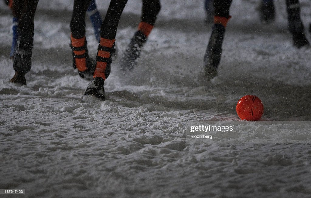 Players run for the ball at the annual Klosters Snow Polo event in Klosters, Switzerland, on Friday, Jan. 20, 2012. German Chancellor Angela Merkel will open next week's World Economic Forum in Davos, Switzerland, which will be attended by policy makers and business leaders including U.S. Treasury Secretary Timothy F. Geithner. Photographer: Scott Eells/Bloomberg via Getty Images