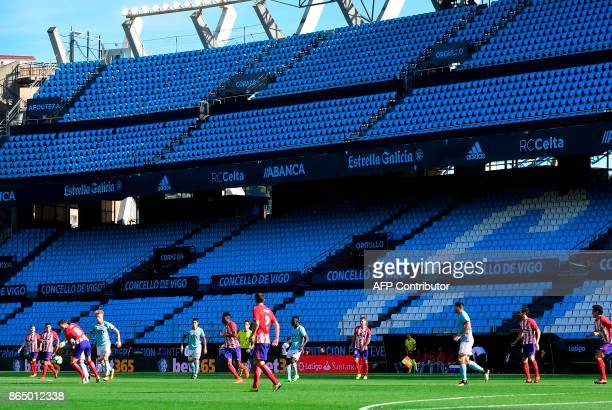 Players run in front of an empty grandstand closed for security reasons during the Spanish league football match RC Celta de Vigo vs Club Atletico de...