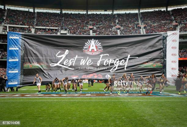 Players run through a joint banner during the 2017 AFL round 05 ANZAC Day match between the Essendon Bombers and the Collingwood Magpies at the...