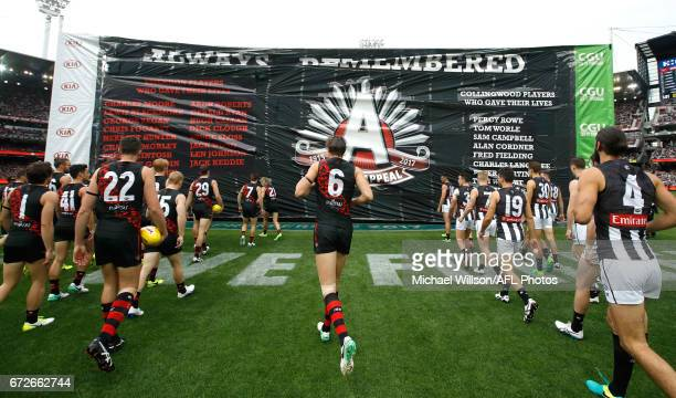 Players run through the joint banner during the 2017 AFL round 05 ANZAC Day match between the Essendon Bombers and the Collingwood Magpies at the...