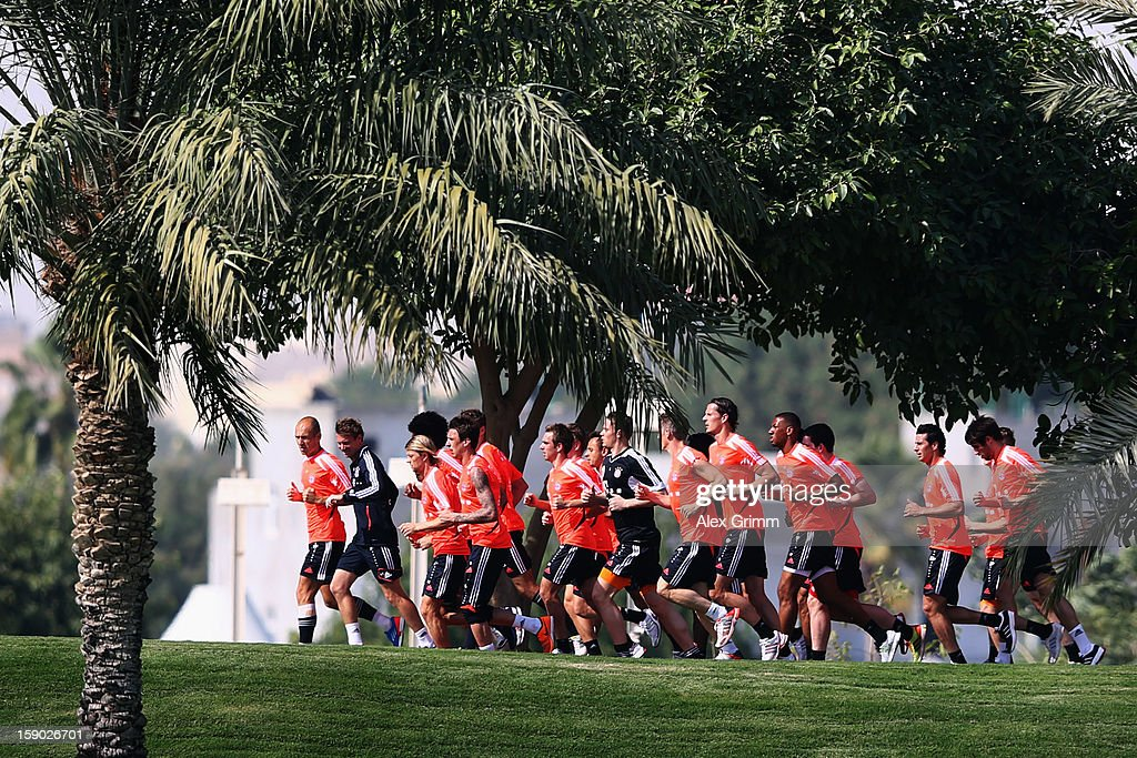 Players run under palms during a Bayern Muenchen training session at the ASPIRE Academy for Sports Excellence on January 6, 2013 in Doha, Qatar.