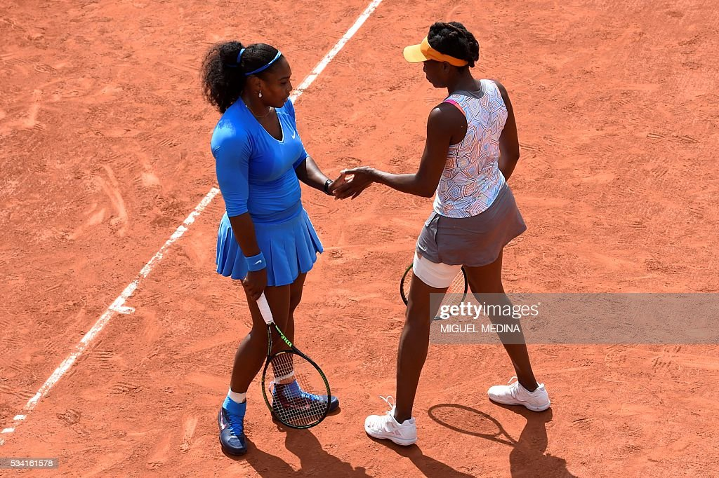 US players Serena Williams (L) and Venus Williams (R) celebrate winning a point during their women's first round double match against Latvia's Jelena Ostapenko and Kazakhstan's Yulia Putintseva at the Roland Garros 2016 French Tennis Open in Paris on May 25, 2016. / AFP / MIGUEL