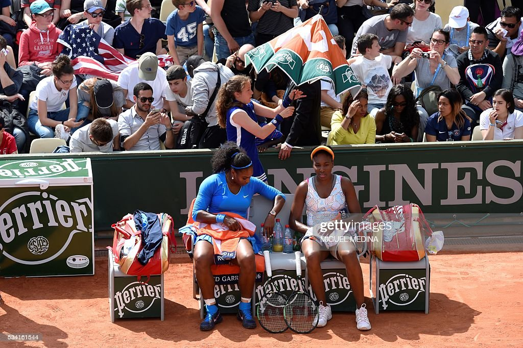 US players Serena Williams (2nd R) and Venus Williams (R) rest during their women's first round double match against Latvia's Jelena Ostapenko and Kazakhstan's Yulia Putintseva at the Roland Garros 2016 French Tennis Open in Paris on May 25, 2016. / AFP / MIGUEL