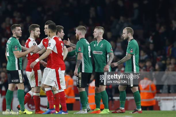 Players shake hands at the end of the English FA cup quarter final football match between Arsenal and Lincoln City at The Emirates Stadium in London...