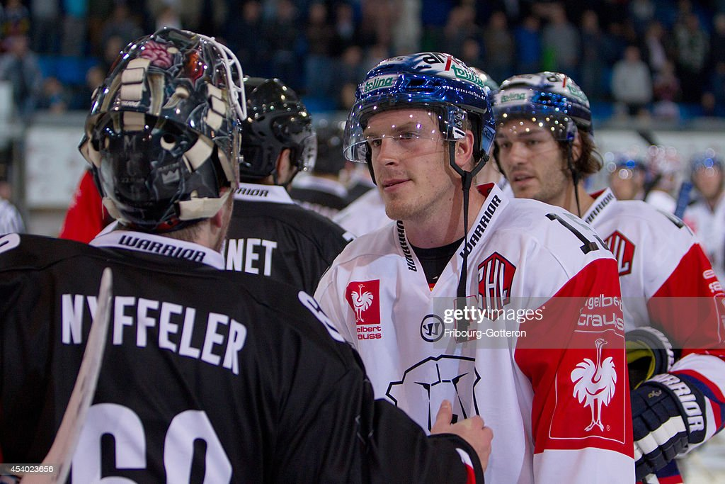 Players shake hands during the group stage match between Fribourg-Gotteron and Eisbaeren Berlin on August 23, 2014 in Fribourg, Switzerland.