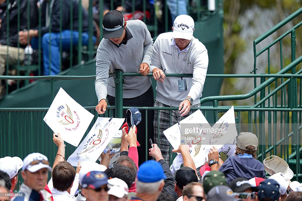 Players sign autographs for fans during a practice round prior to the start of the 112th U.S. Open at The Olympic Club on June 13, 2012 in San Francisco, California.