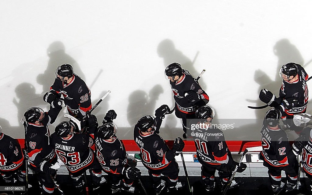 Players skate back to the bench after a goal by Patrick Dwyer #39 of the Carolina Hurricanes with assists from Jay McClement #18 and Brad Malone #24 during their NHL game against the Boston Bruins at PNC Arena on January 4, 2015 in Raleigh, North Carolina.