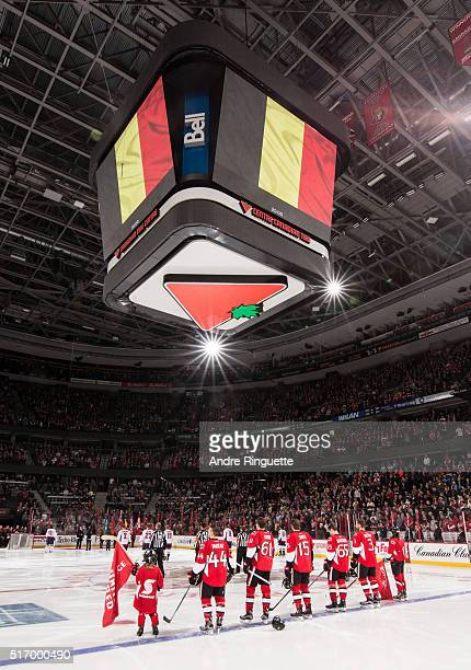 Players stand at attention as the Belgian nation anthem is played prior to an NHL game between the Ottawa Senators and the Washington Capitals at...