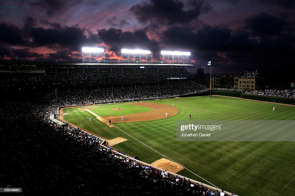 Players stand on the field while the sun sets as the Chicago Cubs take on the Los Angeles Dodgers on August 30, 2005 at Wrigley Field in Chicago, Illinois.
