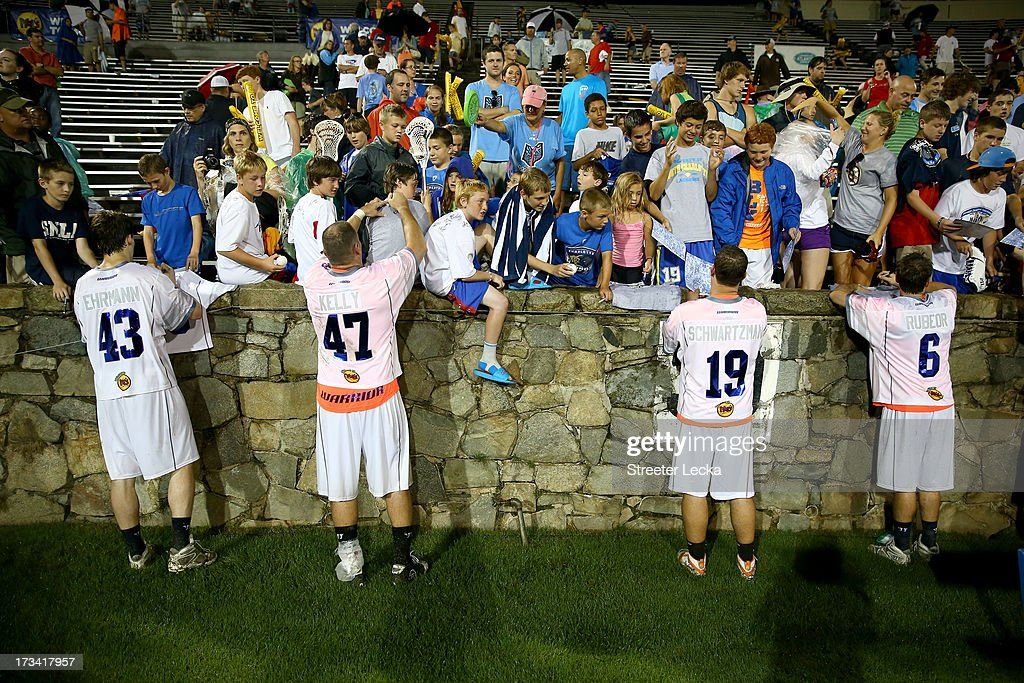 Players stay after the game to sign autographs for fans at the 2013 Major League Lacrosse All Star Game at American Legion Memorial Stadium on July 13, 2013 in Charlotte, North Carolina.