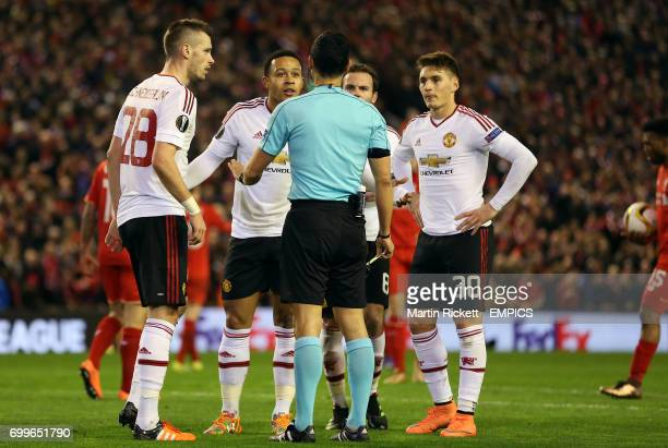 Players surround referee Carlos Velasco after Manchester United's Memphis Depay conceeds a penalty