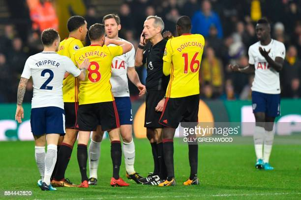 Players surround referee Martin Atkinson after he sent off Tottenham Hotspur's Colombian defender Davinson Sanchez for a challenge on Watford's...