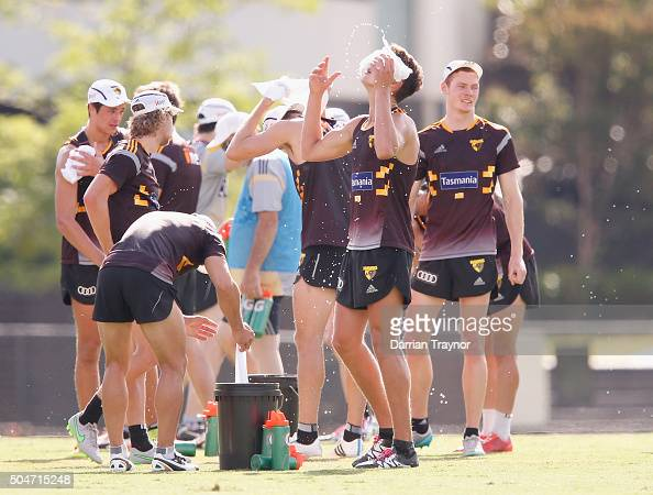 Players use wet towls to cool down during a Hawthorn Hawks AFL preseason training session at Waverley Park on January 13 2016 in Melbourne Australia