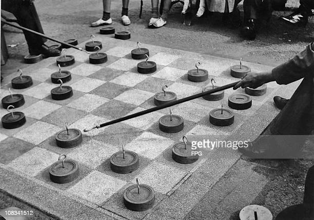 Players using hooked rods to move the pieces on a tiled draughtboard on the promenade at Saltcoats on the Ayrshire coast Scotland circa 1935