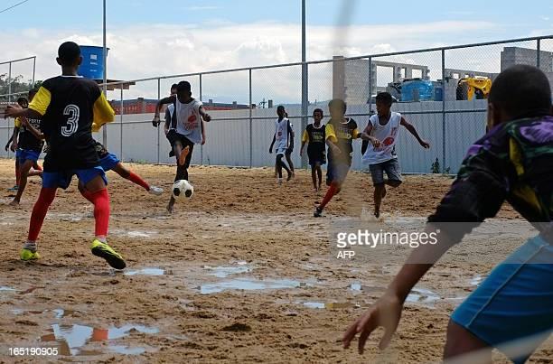 Players vie for the ball during Easter football tournament match in the Campo do Cruzeiro stadium of the Cidade de Deus shantytown in Rio de Janeiro...