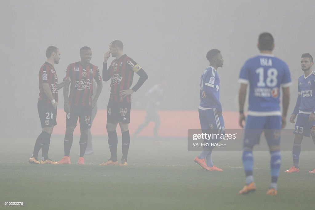 Players wait as the match is interrupted due to smoke bombs during the French L1 football match Nice (OGC Nice) vs Marseille (OM) on February 14, 2016 at the 'Allianz Riviera' stadium in Nice, southeastern France. AFP PHOTO / VALERY HACHE / AFP / VALERY HACHE