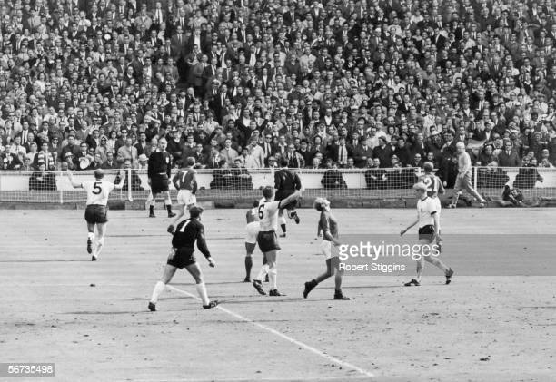 Players wait for the referee's decision after Geoff Hurst's controversial third goal for England during the World Cup Final match against West...