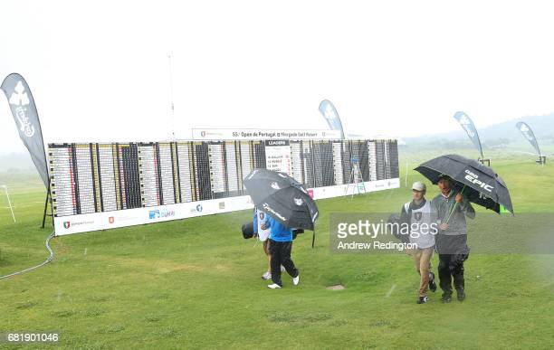 Players walk off the course as play is suspended due to heavy rain during the first round of the Open de Portugal at the Morgado Golf Resort on May...