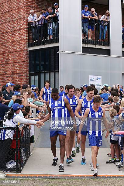 Players walk out to ground past fans during a North Melbourne Kangaroos AFL preseason training session at Aegis Park on December 14 2013 in Melbourne...