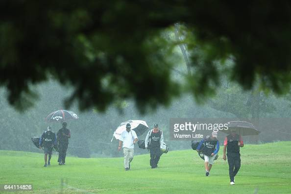 Players walk up the 18th hole as the rain falls during the first round of the Joburg Open at Royal Johannesburg and Kensington Golf Club on February...