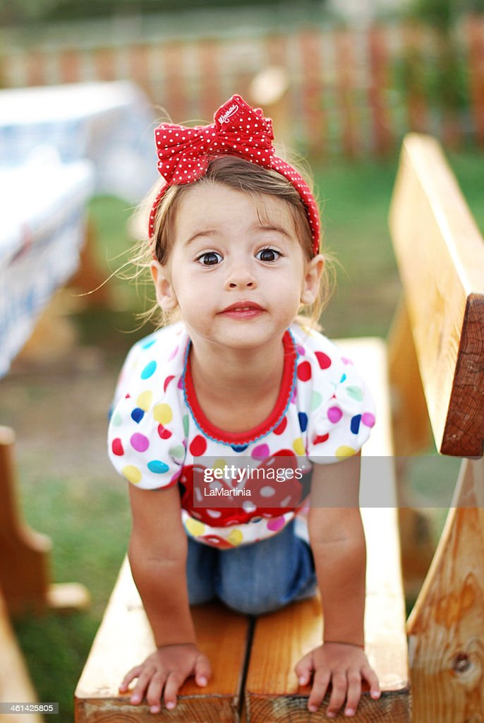 Playful 2 year old girl on a bench : Stock Photo