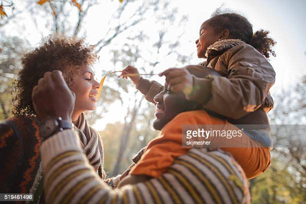 Playful African American family enjoying in nature during autumn.
