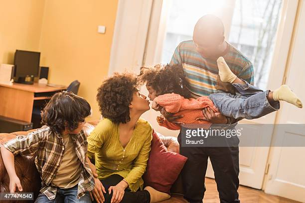 Playful African American family having fun at home.