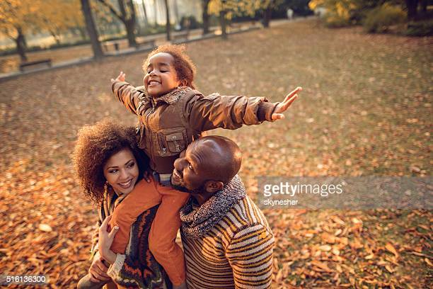 Playful African American little girl having fun with parents outdoors.