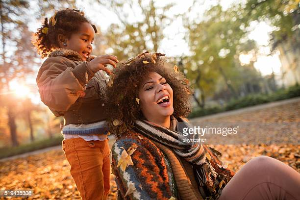 Playful African American mother and daughter having fun in autum.