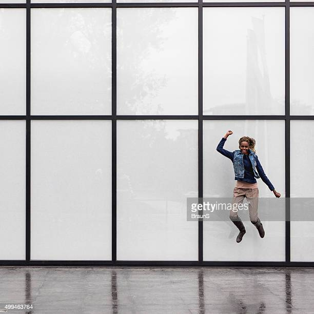 Playful African American woman jumping against curtain wall.