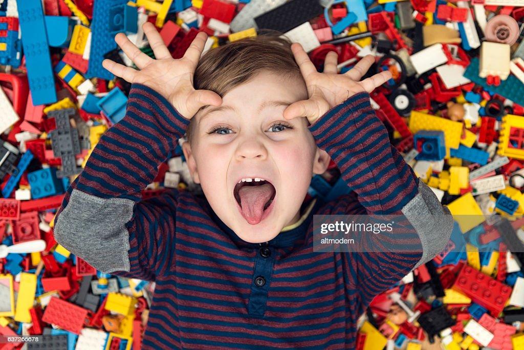 playful boy between plastic blocks : Stock Photo