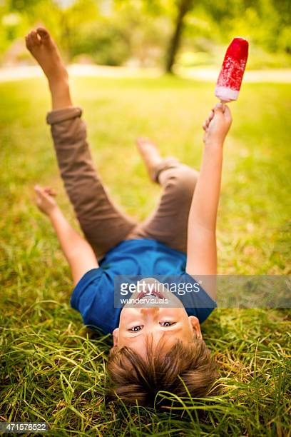 Playful boy having fun eating his ice cream in park