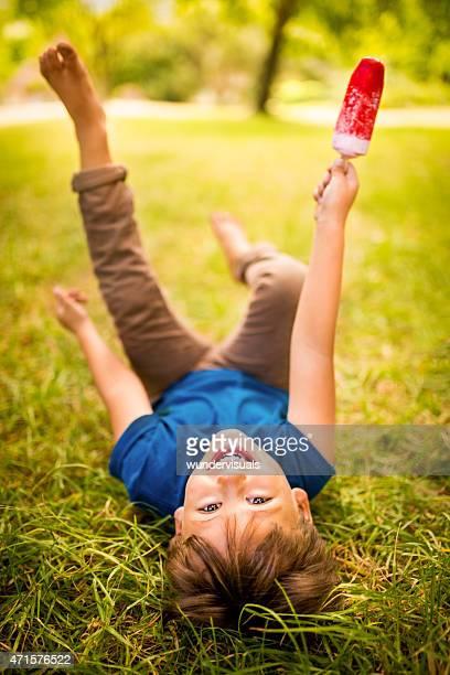 Espiègle garçon s'amusant mangeant sa crème glacée au park