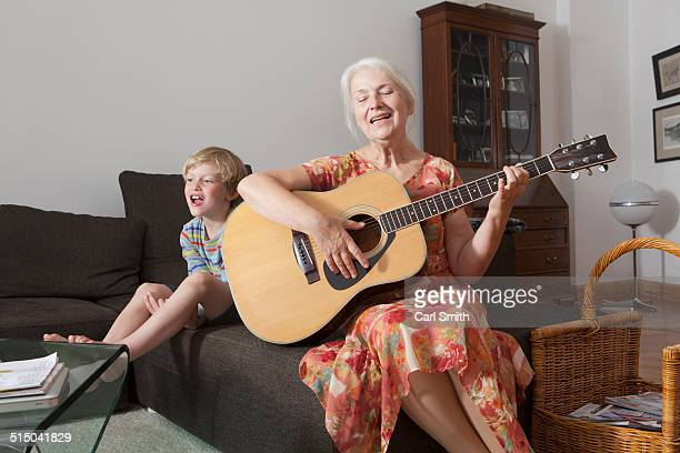 Playful boy sitting with grandmother singing while playing guitar on sofa at home