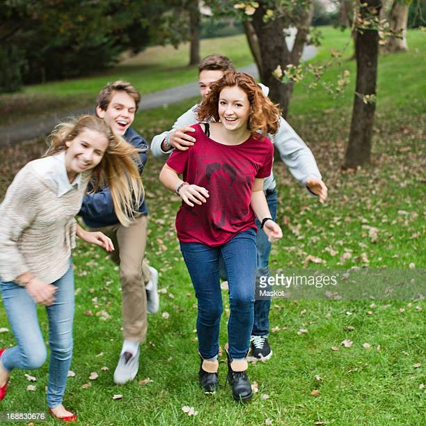 Playful boys chasing female friends at park