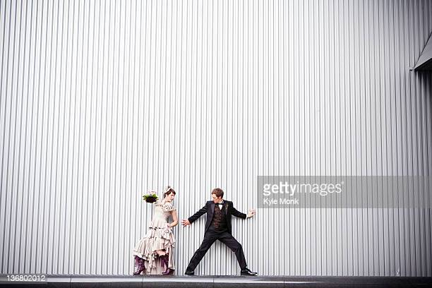 Playful bride and groom standing near wall