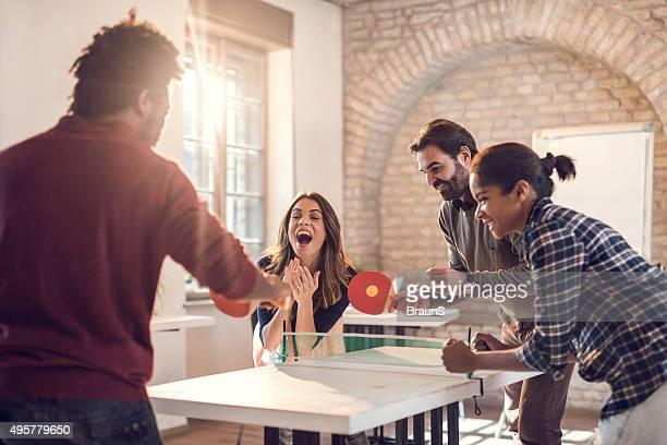 Verspielte business team spielt Tischtennis im legeren Büro.