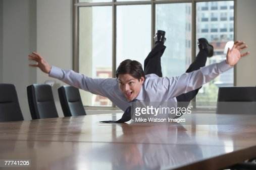 Playful Businessman Laying on Table : Foto de stock