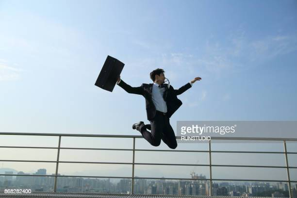 Playful businessman with briefcase jumping