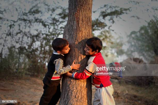 Playful children holding tree trunk