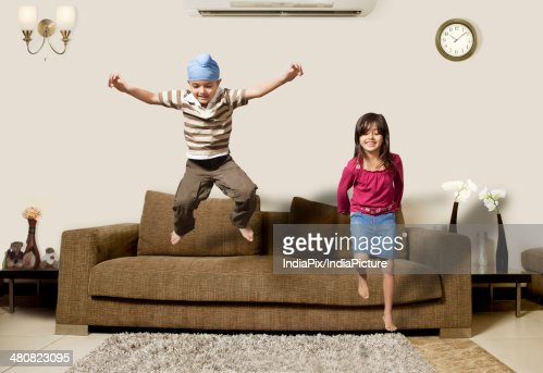 Playful Children Jumping On Sofa In Living Room Stock