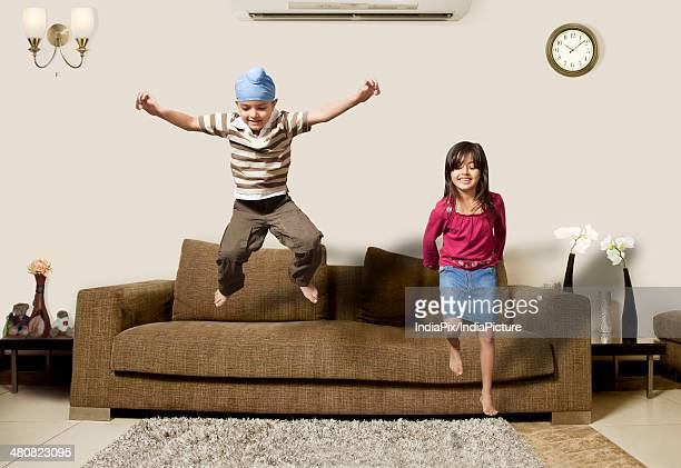 Playful children jumping on sofa in living room