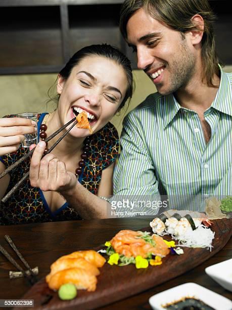 Playful Couple Eating Sushi